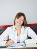 Scolara adolescente felice che si siede allo scrittorio Immagini Stock Libere da Diritti