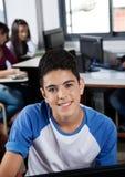 Scolara adolescente felice che si siede nel laboratorio del computer Immagine Stock