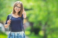 Scolara adolescente giovane attraente che mostra i pollici su Immagini Stock