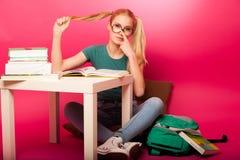 Scolara allegra con due code dei capelli che si siedono sul pavimento dietro la t Fotografie Stock Libere da Diritti