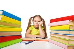 Scolara annoiata con il mucchio dei libri. compito Fotografia Stock