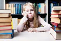 Scolara annoiata e stanca che studia con un mucchio dei libri Fotografia Stock Libera da Diritti