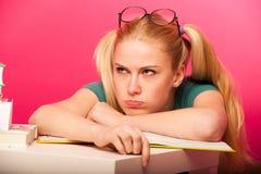 Scolara arrabbiata e annoiata con due code dei capelli e grandi occhiali l Immagini Stock