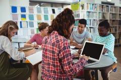 Scolara attenta che utilizza computer portatile con i suoi compagni di classe nello studio del fondo Fotografia Stock