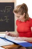 Scolara caucasica dallo scrittorio che studia l'esame di per la matematica Immagini Stock