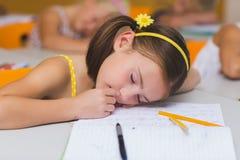 Scolara che dorme allo scrittorio Fotografia Stock