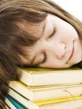 Scolara che dorme sui libri di banco Immagini Stock Libere da Diritti