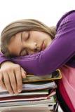 Scolara che dorme sul sacchetto e sui libri di banco Fotografia Stock