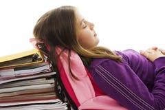 Scolara che dorme sul sacchetto e sui libri di banco Fotografie Stock