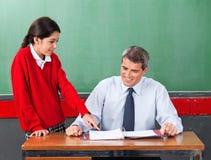 Scolara che fa domanda all'insegnante At Desk Fotografie Stock Libere da Diritti