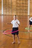 Scolara che gioca con il hula-hoop nella palestra della scuola Fotografia Stock