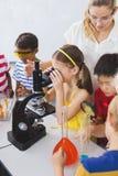 Scolara che guarda tramite il microscopio in laboratorio Fotografie Stock