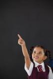 Scolara che indica contro la lavagna in aula Fotografia Stock