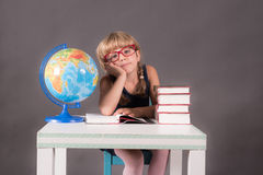 Scolara che indossa i grandi vetri rossi che si appoggiano una tavola con i libri Fotografie Stock