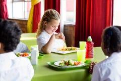 Scolara che mangia alimento con i compagni di classe Fotografie Stock