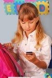 Scolara che per mezzo del telefono mobile Immagini Stock