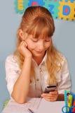 Scolara che per mezzo del telefono mobile durante la lezione Immagine Stock