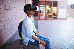Scolara che per mezzo della cuffia avricolare di realtà virtuale Immagini Stock