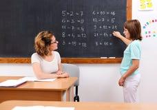 Scolara che risolve le equazioni di per la matematica alla lavagna Immagine Stock Libera da Diritti