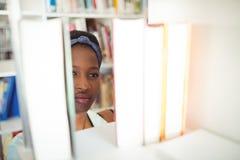 Scolara che seleziona libro a partire dallo scaffale di libro in biblioteca Fotografie Stock Libere da Diritti