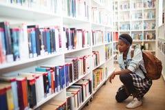 Scolara che seleziona libro a partire dallo scaffale di libro in biblioteca Fotografia Stock