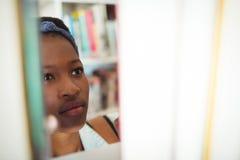 Scolara che seleziona libro a partire dallo scaffale di libro in biblioteca Immagine Stock Libera da Diritti
