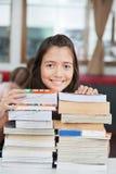Scolara che si appoggia pila di libri in aula Immagini Stock