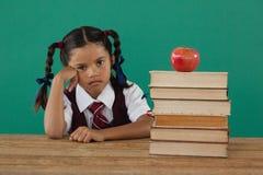 Scolara che si siede accanto alla pila di libri con la mela sulla cima contro la lavagna Immagini Stock Libere da Diritti