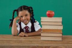 Scolara che si siede accanto alla pila di libri con la mela sulla cima contro la lavagna Immagine Stock