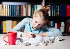 Scolara che si siede alla tavola con la matita a disposizione Fotografie Stock Libere da Diritti