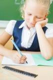 Scolara che si siede allo scrittorio alla scuola e che scrive al taccuino Fotografia Stock