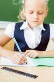 Scolara che si siede allo scrittorio alla scuola e che scrive al taccuino Fotografie Stock Libere da Diritti