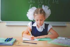 Scolara che si siede allo scrittorio alla scuola e che scrive al taccuino Fotografie Stock