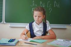 Scolara che si siede allo scrittorio alla scuola e che scrive al taccuino Fotografia Stock Libera da Diritti