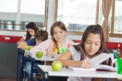 Scolara che si siede allo scrittorio con i compagni di classe in A Fotografia Stock Libera da Diritti