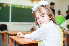 Scolara che si siede allo scrittorio nell'aula della scuola elementare. Fotografia Stock