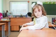 Scolara che si siede allo scrittorio a scuola Immagini Stock
