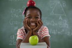 Scolara che si siede con la mela rossa sulla sua testa contro la lavagna Immagine Stock Libera da Diritti