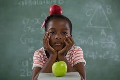 Scolara che si siede con la mela rossa sulla sua testa contro la lavagna Fotografie Stock