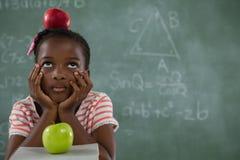 Scolara che si siede con la mela rossa sulla sua testa contro la lavagna Fotografia Stock