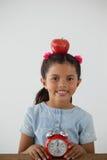 Scolara che si siede con la mela sulla sue testa e sveglia Immagine Stock Libera da Diritti