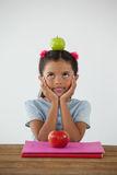 Scolara che si siede con la mela verde sulla sua testa contro il fondo bianco Immagine Stock Libera da Diritti