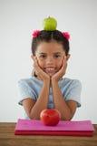 Scolara che si siede con la mela verde sulla sua testa contro il fondo bianco Immagine Stock