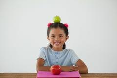 Scolara che si siede con la mela verde sulla sua testa contro il fondo bianco Fotografia Stock