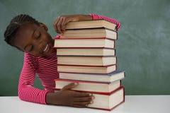Scolara che si siede con la pila di libri contro la lavagna Immagine Stock Libera da Diritti