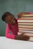 Scolara che si siede con la pila di libri contro la lavagna Fotografia Stock