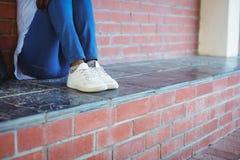 Scolara che si siede contro il muro di mattoni Immagini Stock