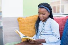 Scolara che si siede sul sofà e sul libro di lettura Fotografia Stock Libera da Diritti