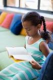 Scolara che si siede sul sofà e sul libro di lettura in biblioteca Fotografia Stock