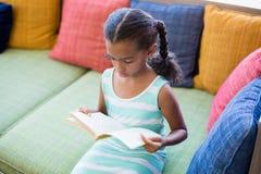 Scolara che si siede sul sofà e sul libro di lettura in biblioteca Immagine Stock Libera da Diritti